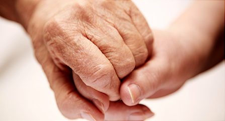 caregiver's hand holding elderly person's hand