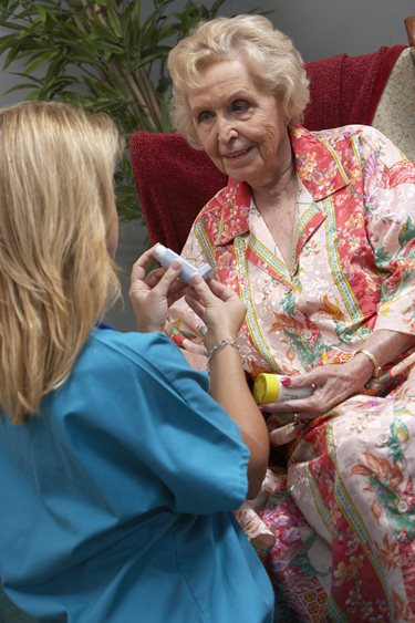 An Interim home care professional teaches her patient how to use her new inhaler