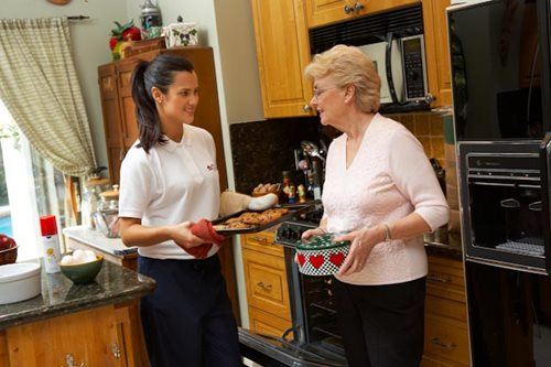 Respite Care professional helps her client bake cookies