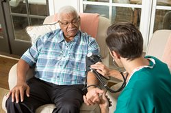 In home nurse takes patients blood pressure - west palm beach and the treasure coast fl