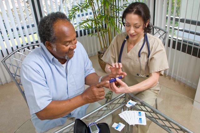 A home care nurse teaches her patient how to use his blood sugar monitor