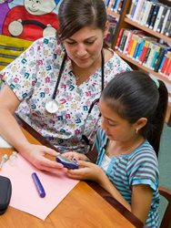 School Nurse Riverhead, NY helps a Diabetic student with her blood monitor