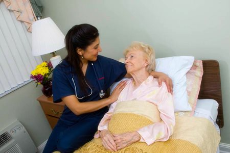 An Interim Hospice Care Nurse sits with her patient