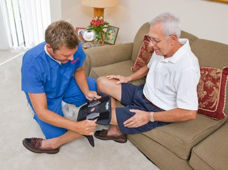 Therapist in the patient's home teaches him how to put on his knee brace properly.