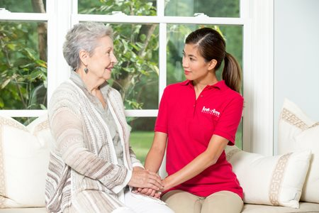 Interim Hospice Care professional, sits with her client