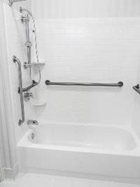 This grab bar layout, shown on a typical bath surround, features a vertical bar at the entry point, another next to the faucets and another on the wall for steadying.